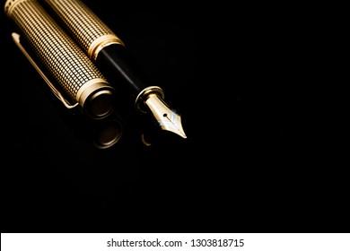 Goldener Stift auf dunklem einzeln Hintergrund