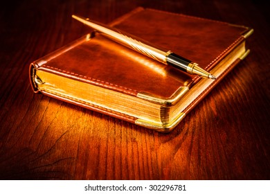 Golden pen on a leather diary on a mahogany table. Image vignetting and hard tones