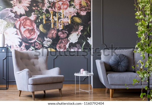 Golden pendant light above a cozy armchair in a fancy living room interior with molding and floral print on gray walls