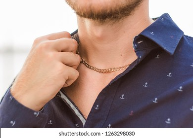 golden pendant on the neck of a man, a man in a shirt