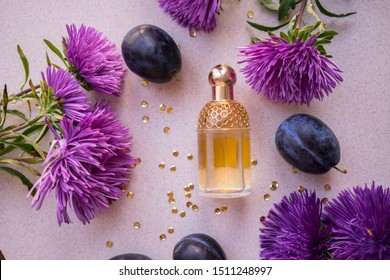 golden perfume bottle with purple asters, blue plums and gold sequins