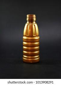 A golden PET bottle in black background