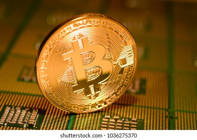 Golden phisical bitcoin over aligned cpu processors. cryptocurrency background.