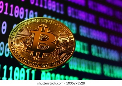 Golden phisical bitcoin over binary colored code. cryptocurrency background.