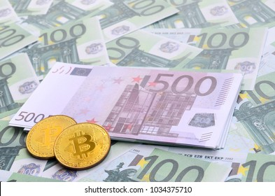 Golden physical bitcoins is lies on a set of green monetary denominations of 100 euros. A lot of money forms an infinite heap