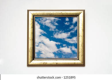 golden picture frame with cloudscape shot on white wall, cloudscape photo is mine