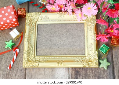 Golden picture frame and gift decoration on wooden background