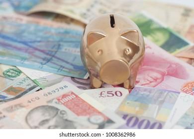 Golden piggy bank with International currencies