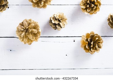 golden pine cones Christmas decoration on white wood table background