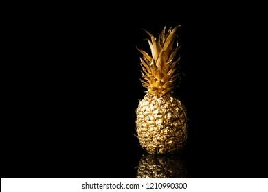 Golden pineapple on black background