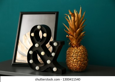 Golden pineapple with stylish decor on table near color wall