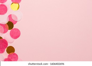 Golden and pink confetti on pink color paper background minimal style macro view with copyspace