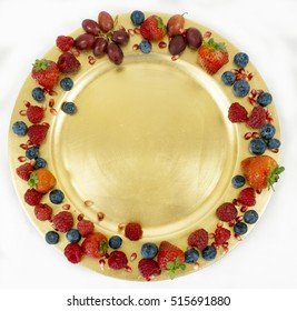 Golden plate with fruit around the edge. strawberries, blueberries, raspberries, pomegranate seeds, grapes. Space for copy.