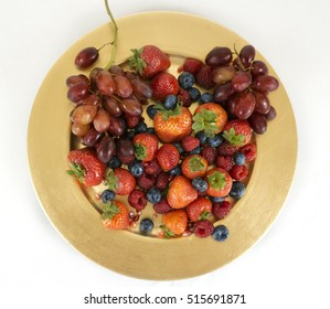 Golden plate full with fruit such as strawberries, blueberries, raspberries, pomegranate seeds, and grapes.