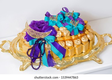 golden plate of khoncha chocolates decorated with purple and turquoise ribbon