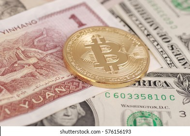 Golden plated bitcoin on yuan note and dollar bills.