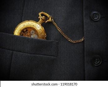 Golden pocket watch in pocket of black men's waistcoat. Low-key image.