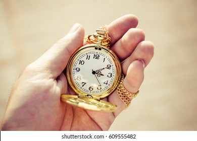 Golden pocket watch in hand close up.
