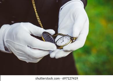 Golden pocket watch in hand, in white gloves