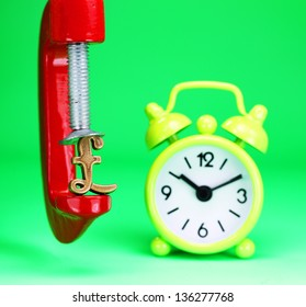 A golden Pound symbol placed in a red clamp with a pastel green background, with a yellow alarm clock in the background indicating the pressure on pound.