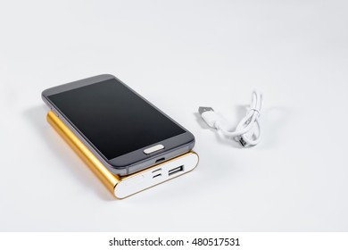 Golden powerbank with smart phone on background