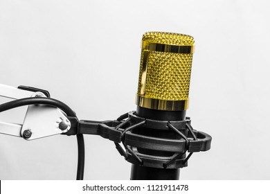 Golden professional studio condenser microphone in the anti vibration holder protrudes from the bottom of the screen isolated on white background