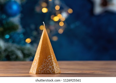 Golden pyramid shaped candle on wooden tablr and blue background with city lights