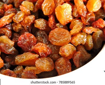 Golden raisins in a white bowl. Close up.