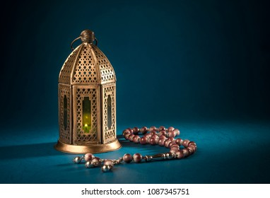 A golden Ramadhan lamp with Islamic rosary beads on dark background. Ramadan - an important Islamic festival. Islamic festive greeting card photo.