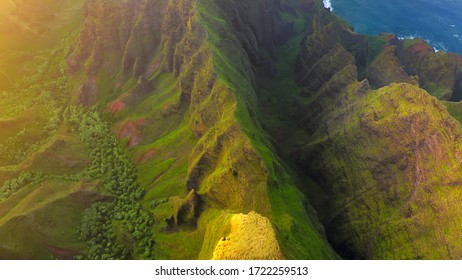 Golden rays of setting sun dramatically illuminate fantastic terrain of Hawaiian coast. Ribbed rocky ridges overgrown with tropical greenery stretch to the very shore of Pacific Ocean. Aerial shot, 4K