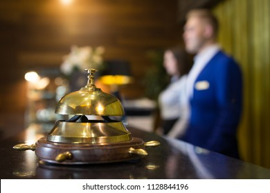 The golden reception bell is at the reception of a five-star hotel on the background of two administrators