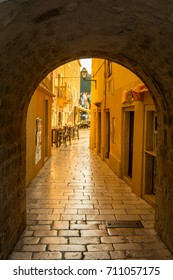 Golden reflection of first sun rays in the narrow street at town Rab