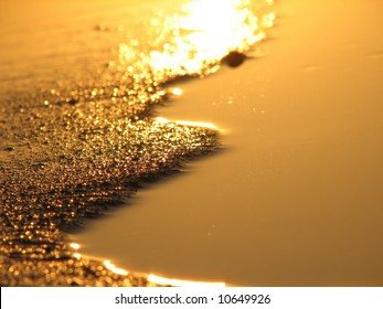 Golden reflection of the sunset in the sand.