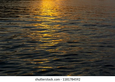 Golden reflections of setting sun on sea water for background