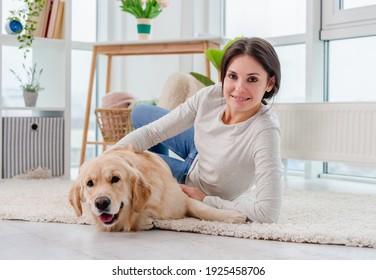Golden retriever dog lying next to girl on floor at home