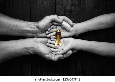 golden ribbon childhood symbol of the fight against cancer in children in hands on a dark background. concept of helping patients with sarcoma and bladder cancer.black and white.