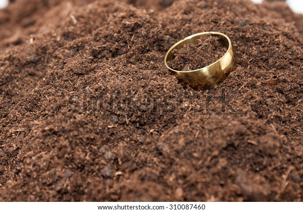 Golden ring droped on the soil ground.