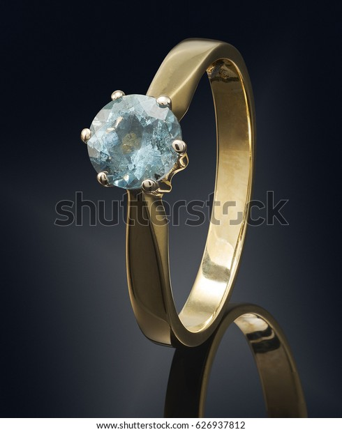 Golden ring with gemstone isolated on black background.