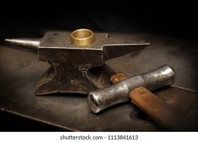 golden ring on an anvil and a goldsmith hammer in the jewelry workshop, still life with copy space in the dark background, selected focus, narrow depth of field