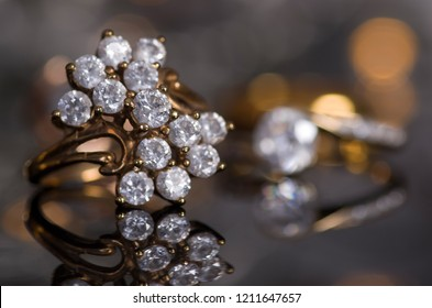 Golden rings on a gray background with a mirror image and lights in the background.