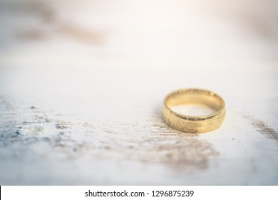 Golden rings, wedding rings of the bride and groom on white vintage wooden background