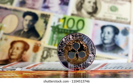 Golden Ripple coin against of different banknotes on background. Cryptocurrency Trading concept .