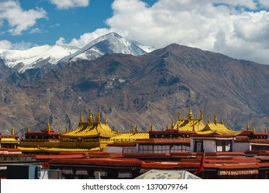 The golden rooftops of Jokhang Temple stand against the snow capped mountains in Lhasa, Tibet.