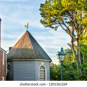 Golden rooster weathervane glinting brightly in golden sunlight atop a conical shaped roof on building with arched window and circular window