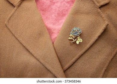 Golden rose brooch on khaki wool coat with pink sweater inside.