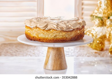"""""""Golden Rose"""" cheesecake with meringue (Polish cake). Whole new york style cheesecake on white plate"""