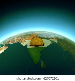 Golden Rupee coin on globe enlightening India representing investment