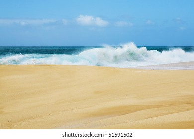 Golden sand and blue surf with a wave crashing along the shore in Hawaii.