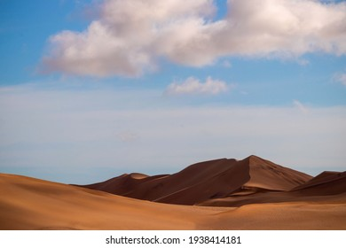 Golden sand dune 7 and white clouds on a sunny day in the Namib desert.