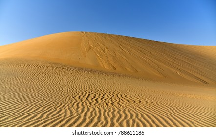 Golden Sand Dunes and Sand Ripples Meet below the Blue Skies of the Arabian Desert, Eastern Province, Kingdom of Saudi Arabia